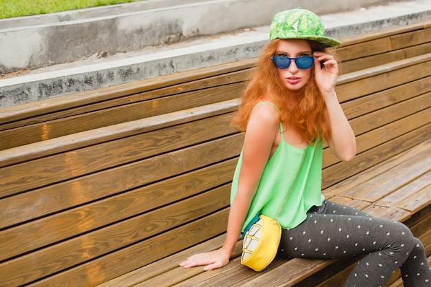 Jonge stijlvolle hipster gember vrouw, zittend op de bank, groene pet, legging, tas, zonnebril, plezier maken, trendy kleding, mode-outfit, stedelijke tienerstijl Gratis Foto