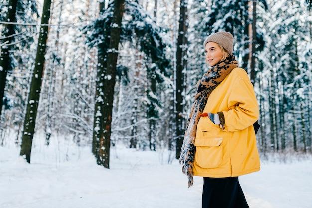 Jonge stijlvolle hipster meisje in gele jas met een warme sjaal poseren in het sneeuwbos Premium Foto