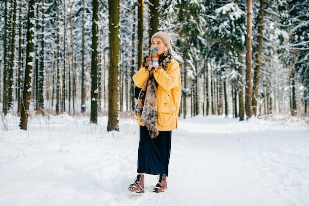 Jonge stijlvolle hipster meisje in gele jas met een warme sjaal wandelen in het sneeuwwoud Premium Foto