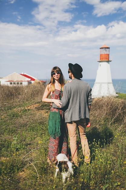Jonge stijlvolle hipster paar verliefd wandelen met de hond op het platteland Gratis Foto