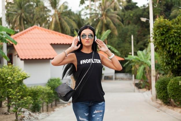 Jonge stijlvolle hipster vrouw in zwart t-shirt, spijkerbroek, luisteren naar muziek op koptelefoon, plezier, wandelen in de straat, zomervakantie, genieten van Gratis Foto