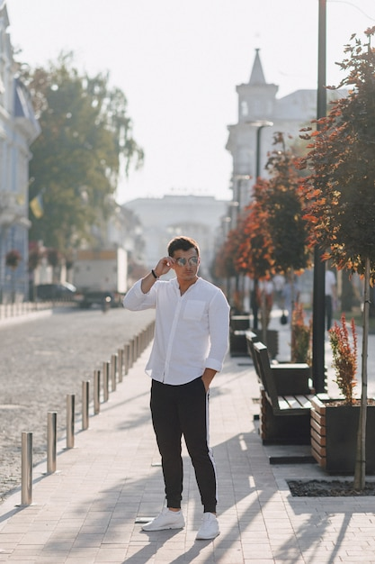 Jonge stijlvolle man in een shirt lopen in een europese straat op een zonnige dag Gratis Foto