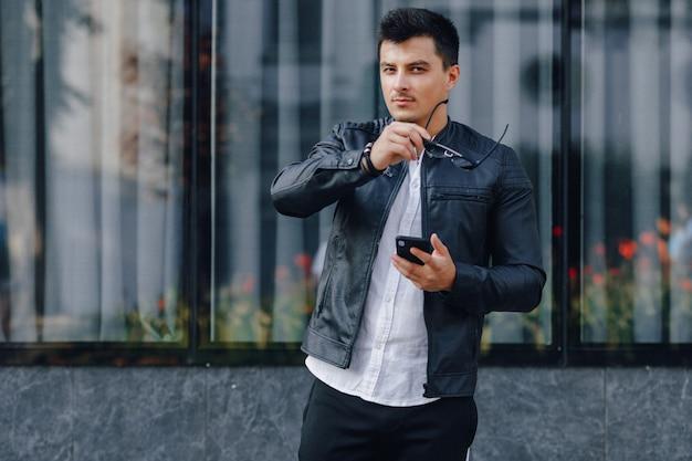 Jonge stijlvolle man in glazen in zwart lederen jas met telefoon op glas achtergrond Gratis Foto