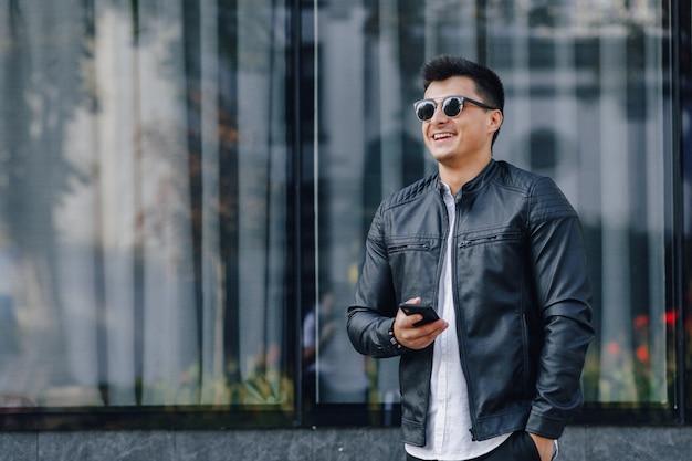 Jonge stijlvolle man in glazen in zwart lederen jas met telefoon Gratis Foto