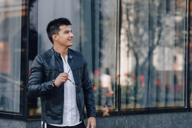 Jonge stijlvolle man in glazen in zwart lederen jas op glazen oppervlak Premium Foto