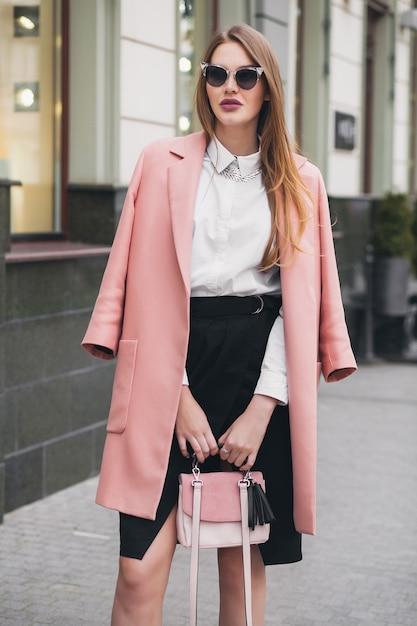 Jonge stijlvolle mooie vrouw die op straat loopt, roze jas draagt, tas, zonnebril, wit overhemd, zwarte rok, mode-outfit, herfsttrend, gelukkig lachend, accessoires Gratis Foto