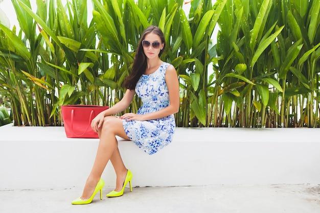 Jonge stijlvolle mooie vrouw in blauwe bedrukte jurk, rode tas, zonnebril, vrolijke stemming, modieuze outfit, trendy kleding, glimlachen, zittend, zomer, gele schoenen met hoge hakken, accessoires Gratis Foto