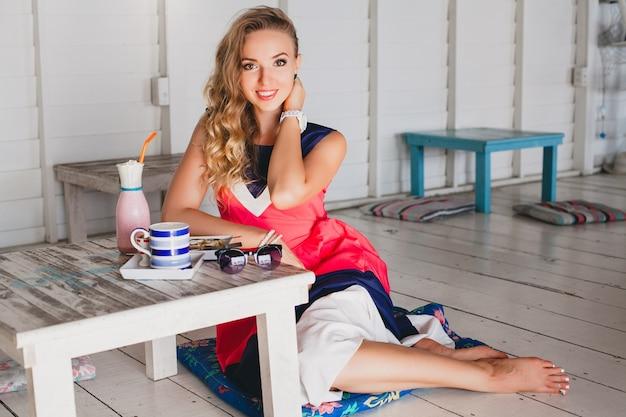 Jonge stijlvolle mooie vrouw in zee café, pannenkoeken eten, cocktail smoothie, zonnebril, flirterige, resortstijl, modieuze outfit, glimlachen, mariene kleuren jurk Gratis Foto