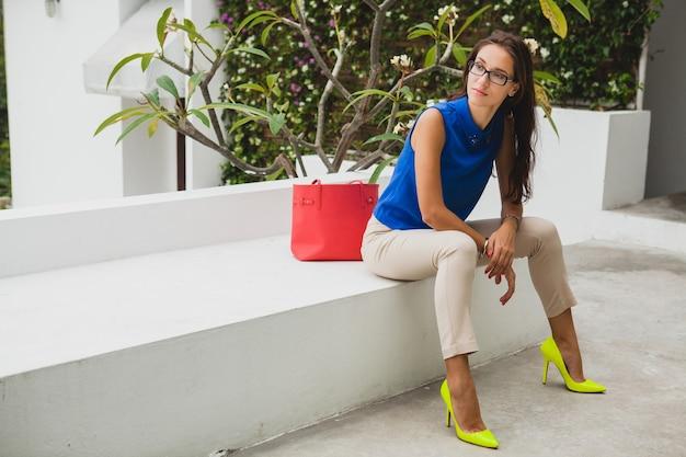 Jonge stijlvolle mooie vrouw, zomer modetrend, blauwe blouse, rode tas, bril, tropische villa resort, vakantie, flirterig, lange slanke benen, broek, gele schoenen, hakken Gratis Foto