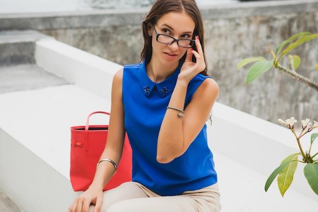 Jonge stijlvolle mooie vrouw, zomer modetrend, blauwe blouse, rode tas, bril, tropische villa resort, vakantie, flirterig Gratis Foto