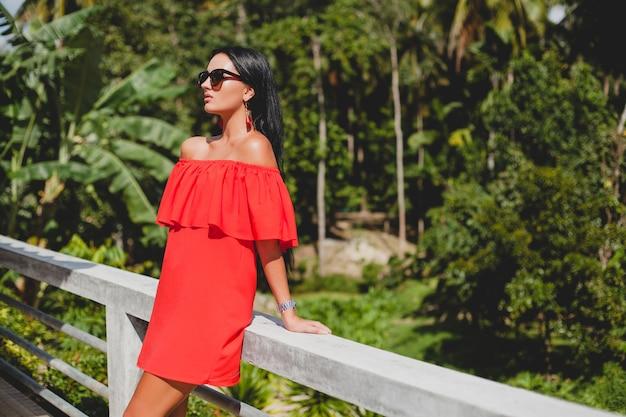 Jonge stijlvolle sexy vrouw in rode zomerjurk staande op terras in tropisch hotel, palmbomen achtergrond, lang zwart haar, zonnebril, etnische oorbellen, zonnebril, glimlachen Gratis Foto