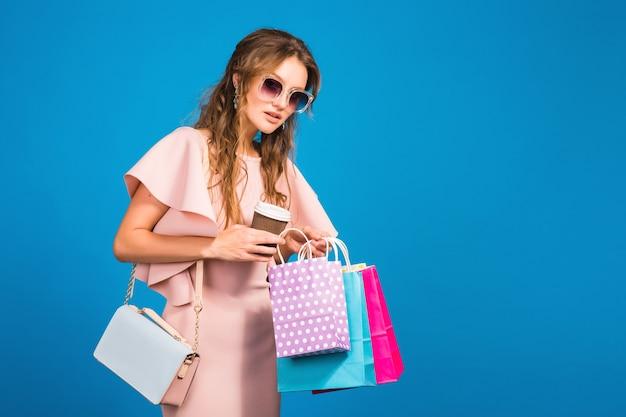 Jonge stijlvolle sexy vrouw in roze luxe jurk, zomer modetrend, chique stijl, zonnebril, blauwe studio achtergrond, winkelen, papieren zakken vasthouden, koffie drinken, shopaholic Gratis Foto