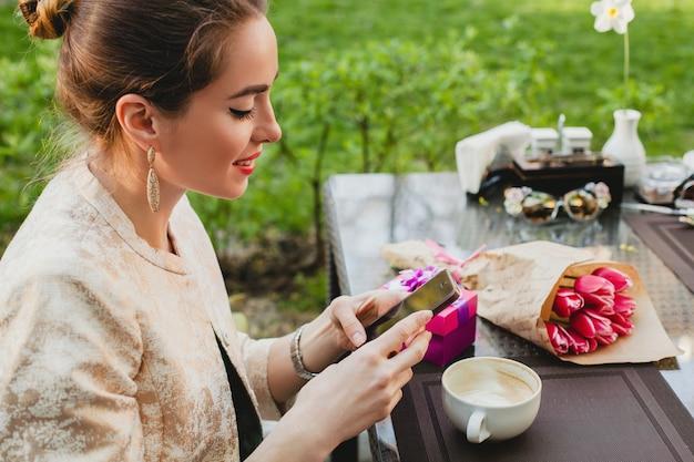Jonge stijlvolle vrouw zitten in café, slimme telefoon te houden Gratis Foto