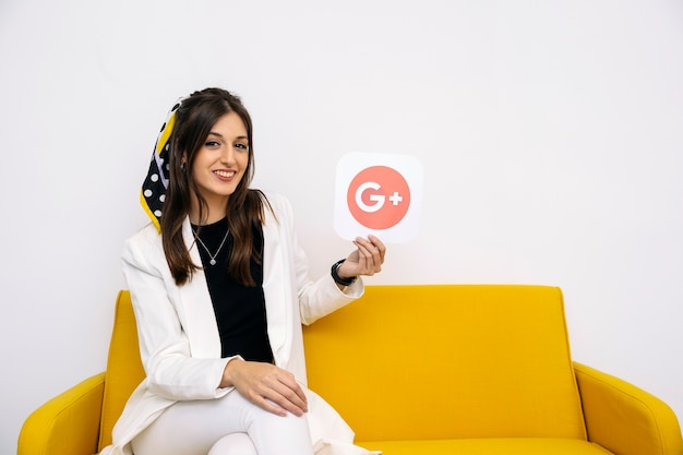 Jonge stijlvolle zakenvrouw weergegeven: google plus pictogram in haar hand Gratis Foto