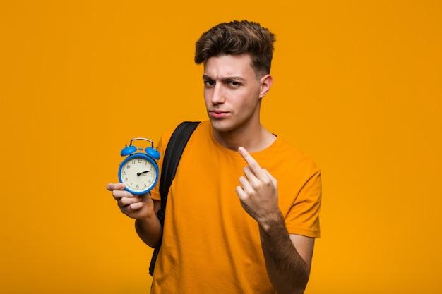Jonge student man met een wekker onder de indruk kopie ruimte op palm te houden. Premium Foto