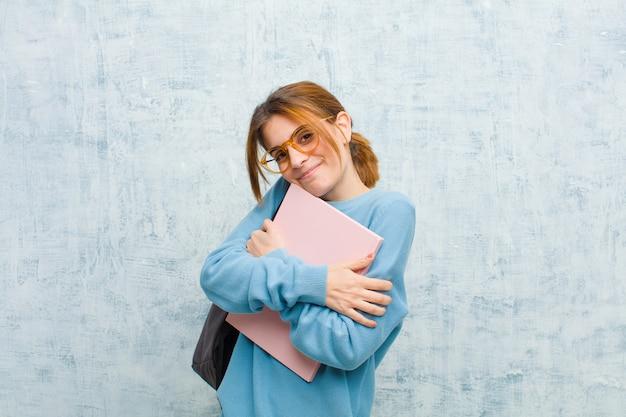 Jonge student vrouw gevoel in liefde, glimlachen, knuffelen en knuffelen zelf, single blijven, egoïstisch en egocentrische grunge muur Premium Foto