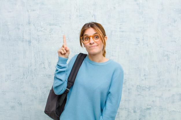 Jonge student vrouw voelt zich als een geniale vinger trots omhoog in de lucht na het realiseren van een geweldig idee, eureka zeggen tegen grunge muur muur Premium Foto