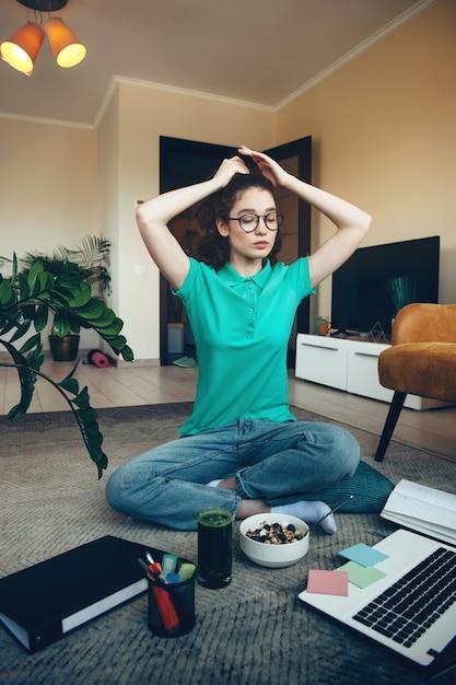 Jonge student zich klaarmaken voor de online lessen zittend op de vloer met een laptop en een bord ontbijtgranen Premium Foto