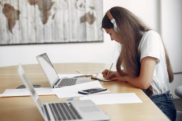 Jonge student zit aan de tafel en gebruik de laptop Gratis Foto