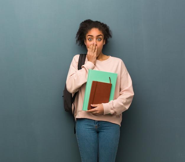 Jonge student zwarte vrouw erg bang en bang verborgen. ze houdt boeken. Premium Foto