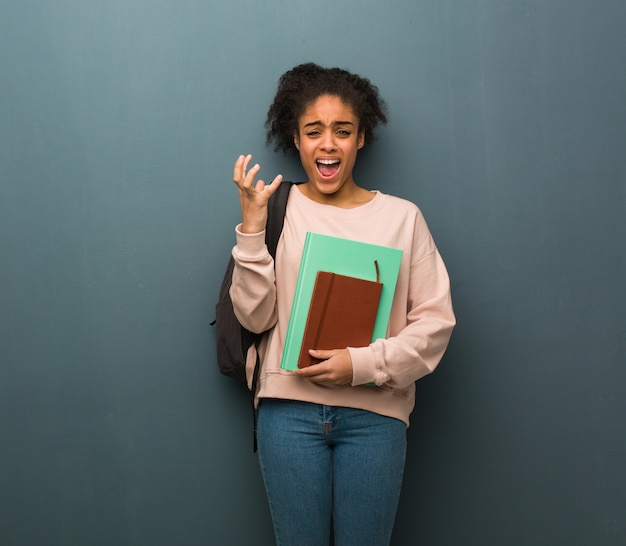 Jonge student zwarte vrouw erg bang en bang. ze houdt boeken vast. Premium Foto