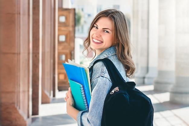 Jonge studente die tegen universiteit glimlacht. de leuke studente houdt omslagen en notitieboekjes in handen. leren, onderwijs Premium Foto