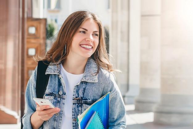 Jonge studente die tegen universiteit glimlacht. leuke studente houdt mappen, laptops en mobiele telefoon in handen. leren, onderwijs Premium Foto
