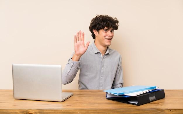 Jonge studentenmens met laptop het groeten met hand met gelukkige uitdrukking Premium Foto