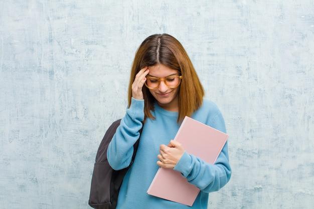 Jonge studentenvrouw die gestrest en gefrustreerd kijkt, werkt onder druk met hoofdpijn en verontrust met problemen Premium Foto