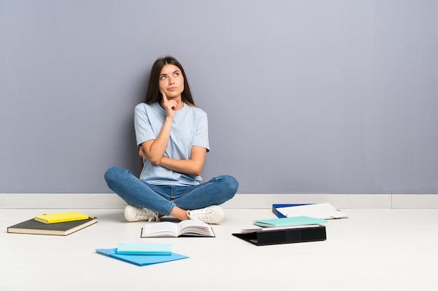 Jonge studentenvrouw die met vele boeken op de vloer een idee denkt Premium Foto