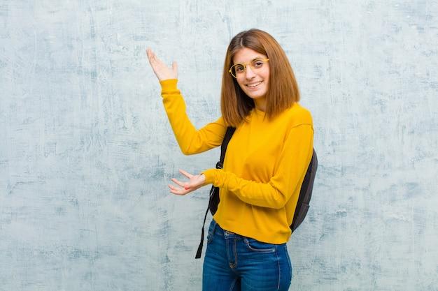 Jonge studentenvrouw die trots en vol vertrouwen glimlachen, gelukkig en tevreden voelen en een concept op exemplaarruimte tonen tegen de muur van de grungemuur Premium Foto