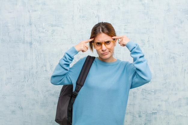 Jonge studentenvrouw met een serieuze en geconcentreerde blik, brainstormend en denkend aan een uitdagend probleem Premium Foto