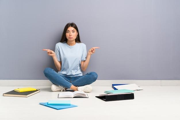 Jonge studentenvrouw met veel boeken op de vloer die naar de zijtakken wijzen die twijfels hebben Premium Foto
