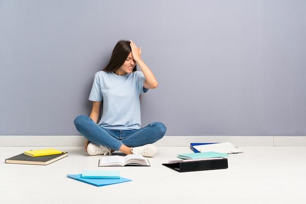 Jonge studentenvrouw met vele boeken op de vloer die twijfels hebben en met gezichtsuitdrukking verwarren Premium Foto