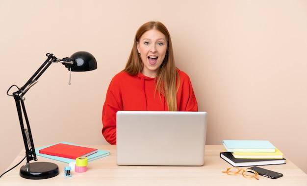 Jonge studentenvrouw op een werkplaats met laptop met verrassingsgelaatsuitdrukking Premium Foto