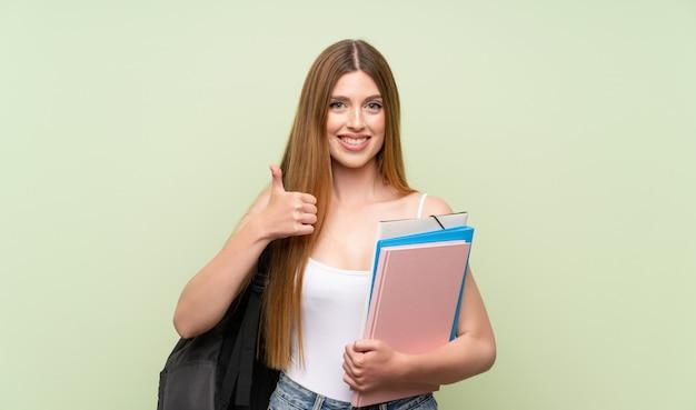 Jonge studentenvrouw over het geïsoleerde groene geven duimen op gebaar Premium Foto