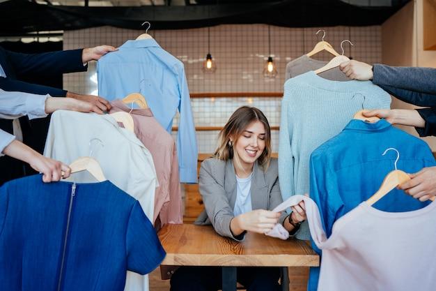 Jonge stylist die door reeks overhemden kijkt voor manier het schieten Gratis Foto