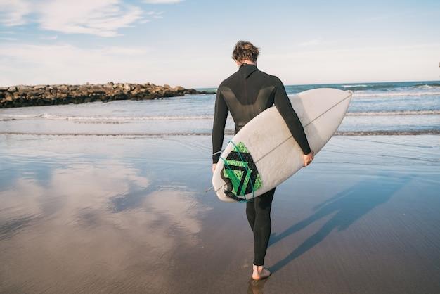 Jonge surfer die het water ingaat met zijn surfplank in een zwart surfpak. sport en watersport concept. Premium Foto