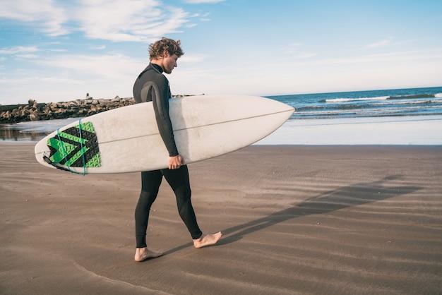 Jonge surfer die zich in de oceaan met zijn surfplank in een zwart surfpak bevindt. sport en watersport concept. Premium Foto