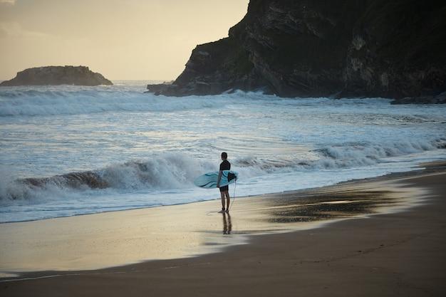 Jonge surfer in kort wetsuit met funboard in de hand blijft bij zonsopgang alleen op het verborgen surfstrand. klaar om de oceaan in te gaan Gratis Foto