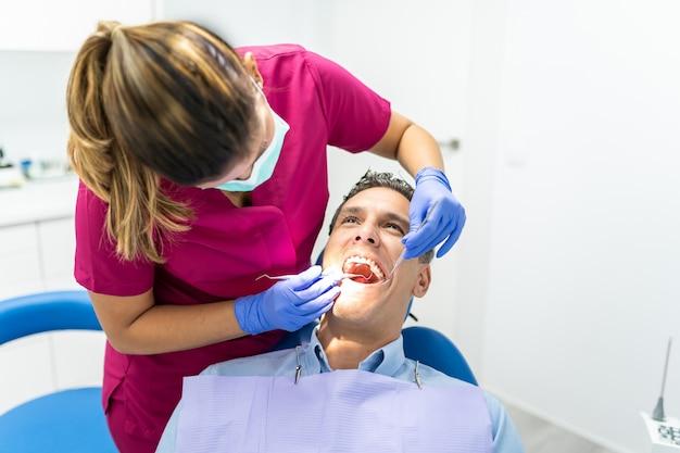 Jonge tandartsvrouw die een controle tot een patiënt doet. Premium Foto