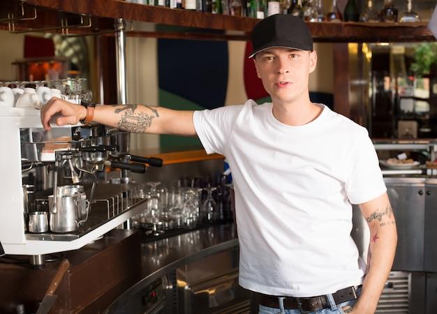 Jonge tattoed serieuze barista die zich naast de op zwaar werk berekende commerciële koffiemachine bevindt. Premium Foto