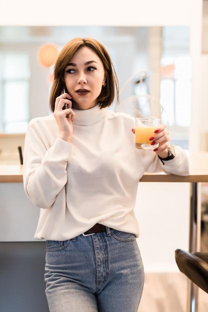 Jonge tedere dame in wit t-shirt en spijkerbroek in de keuken praten aan de telefoon Gratis Foto