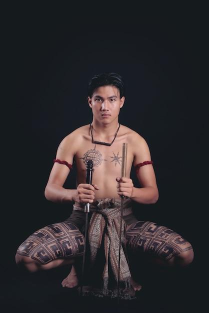 Jonge thailand mannelijke krijger poseren in een vechthouding met een zwaard Gratis Foto