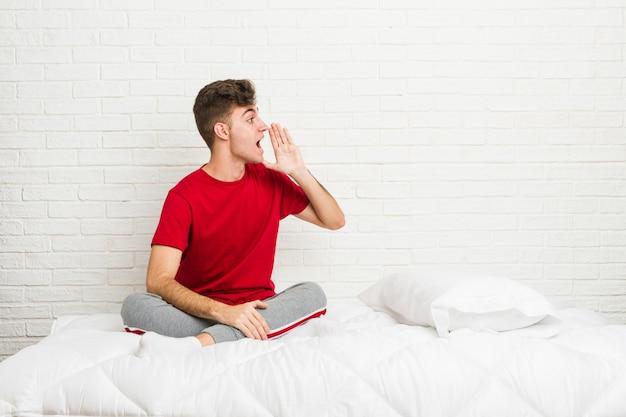 Jonge tiener student man op het bed schreeuwen en houden palm in de buurt van geopende mond. Premium Foto