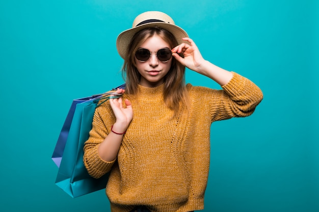 Jonge tienervrouw in zonnebril en hoedenholding het winkelen zakken in haar handen die zo geluk voelen dat op groene muur wordt geïsoleerd Gratis Foto