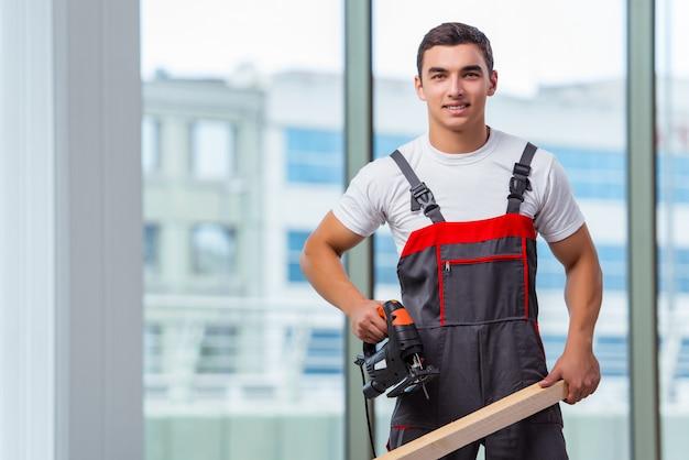Jonge timmerman die bij bouwwerf werkt Premium Foto