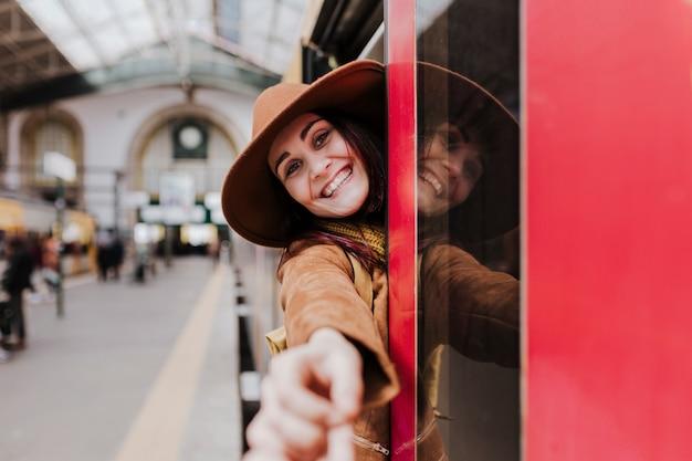 Jonge toeristenvrouw bij stationwachten om een trein en te reizen te nemen. een andere hand vasthouden en naar de camera kijken Premium Foto
