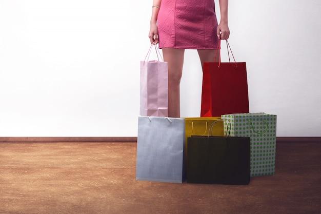 Jonge trendy vrouw die roze kleding met het winkelen zakken draagt Premium Foto