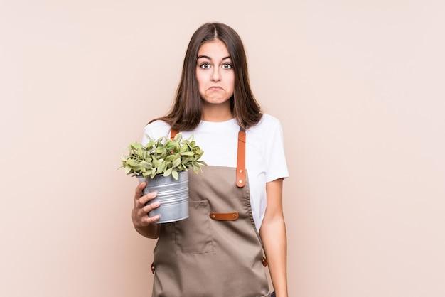 Jonge tuinman blanke vrouw met een plant geïsoleerdhaalt schouders en open ogen verward. Premium Foto